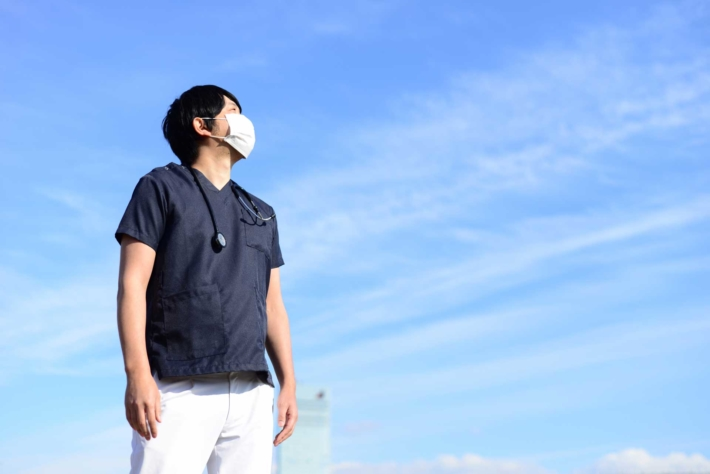 青空を見上げている男性介護スタッフ