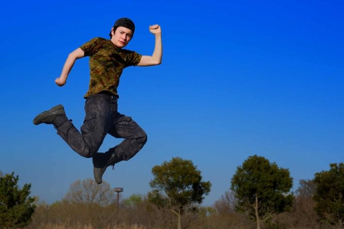 青空を背景にジャンプしてポーズをキメている男性
