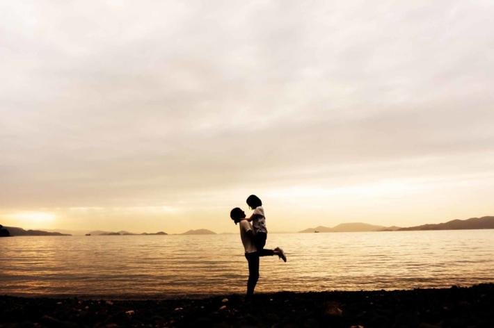 沈む夕焼けを背景に抱きしめ合うカップル