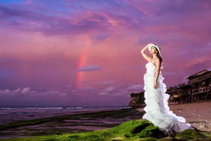 夕焼けを背景に空を見つめるウエディングドレス姿の女性