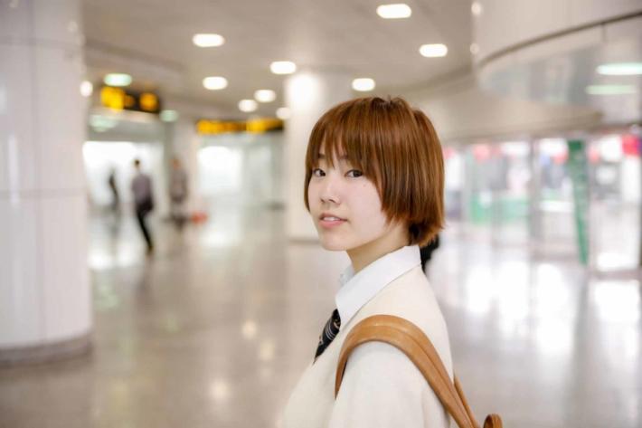 駅の改札で振り返る女子高生
