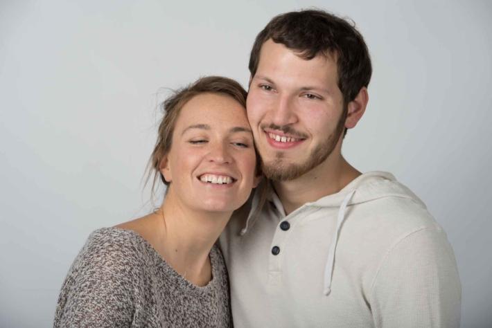頬を寄せ合い笑っている外国人のカップル