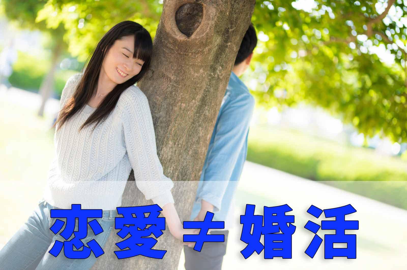 恋愛≠婚活と書かれたテキストと木の幹を挟んで背面で手を繋ぐカップル