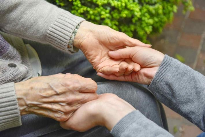 老人の手を取る女性の手