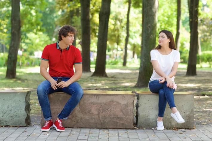 公園で離れて座る男女のカップル