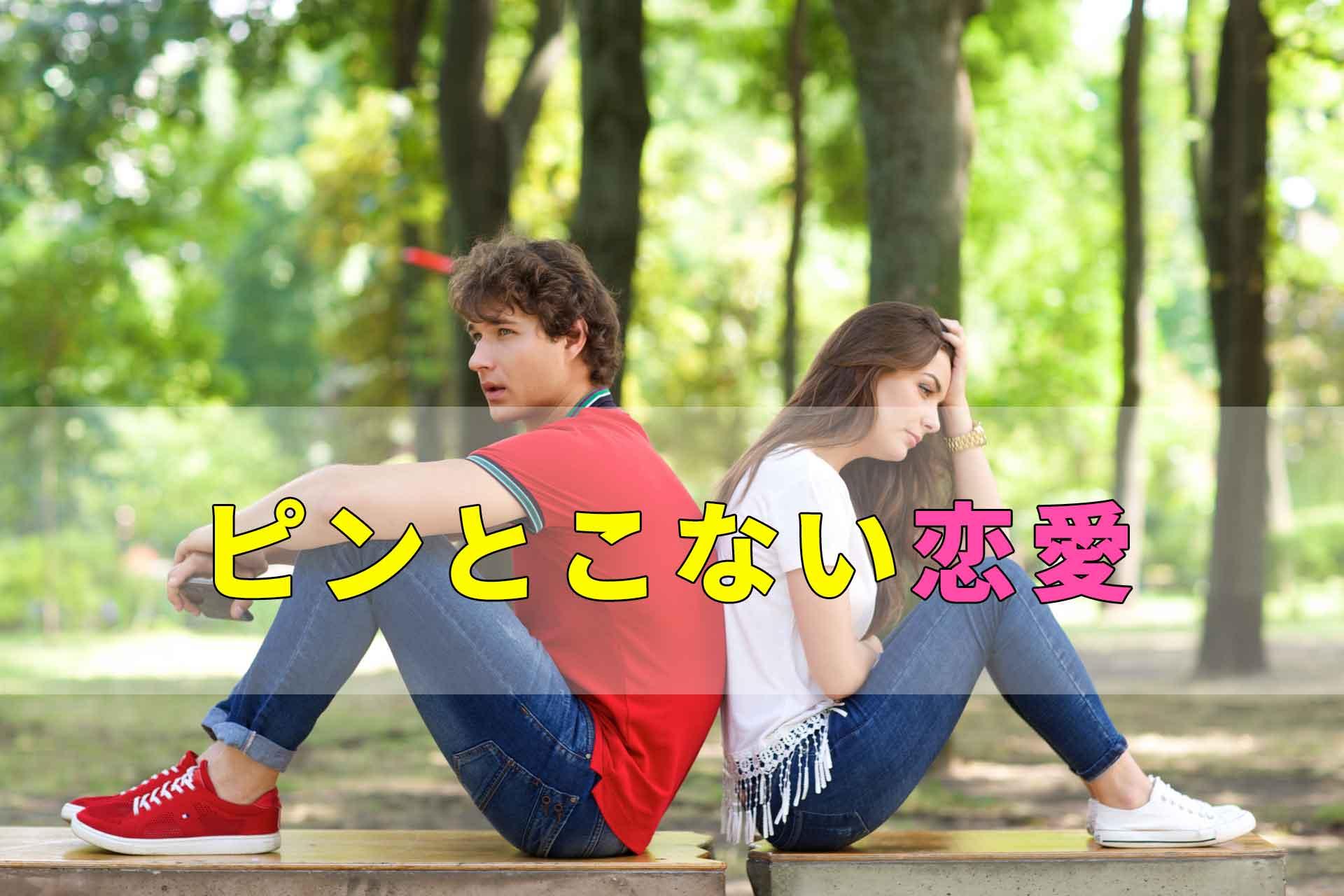 ピンとこない恋愛の文字と公園に背中合わせに座る男女