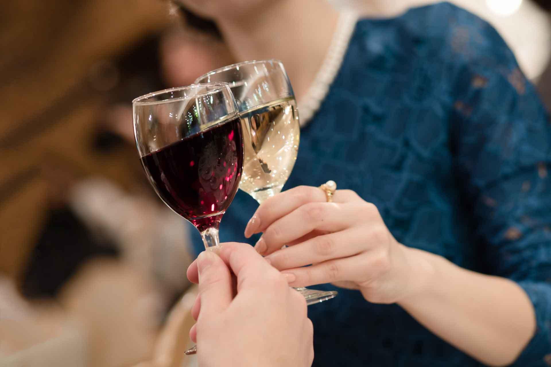 ワイングラスで乾杯する、ドレすあっぷした女性の胸元