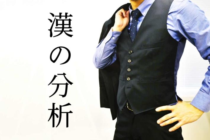「漢の自己分析」と書かれたテキストに手に腰をあてて立つベスト姿の男性