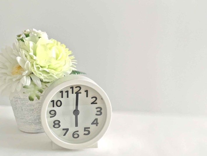 置時計とその後ろに置かれた花