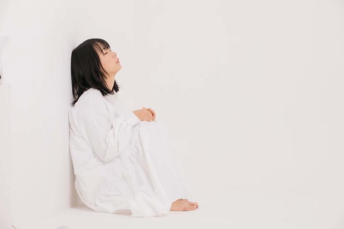 白い部屋で壁にもたれてボーッとしている女性