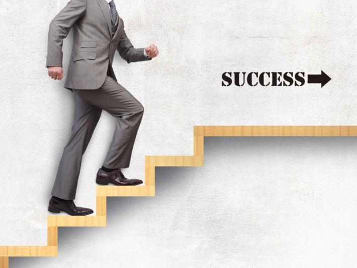 目標に向けて階段のステップを踏むスーツ姿の男性