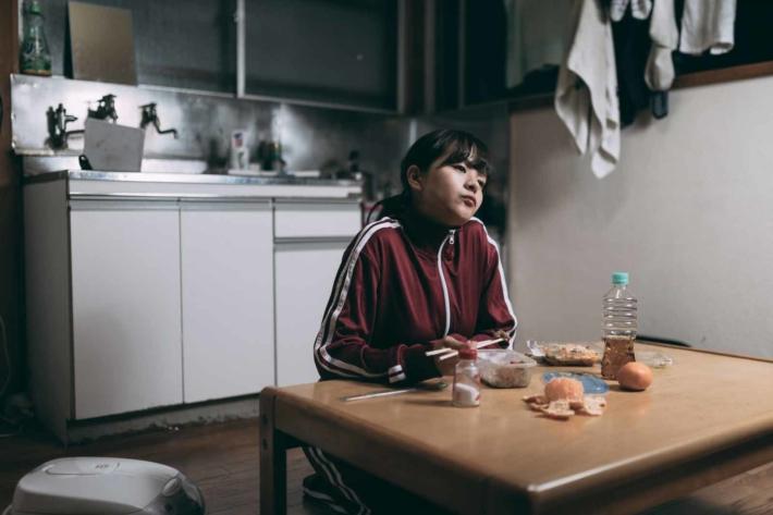 ボロアパートのリビングでジャージ姿でぼーっとしている女性
