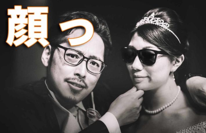 「顔っ」と書かれたテキストと結婚式を挙げているカップル
