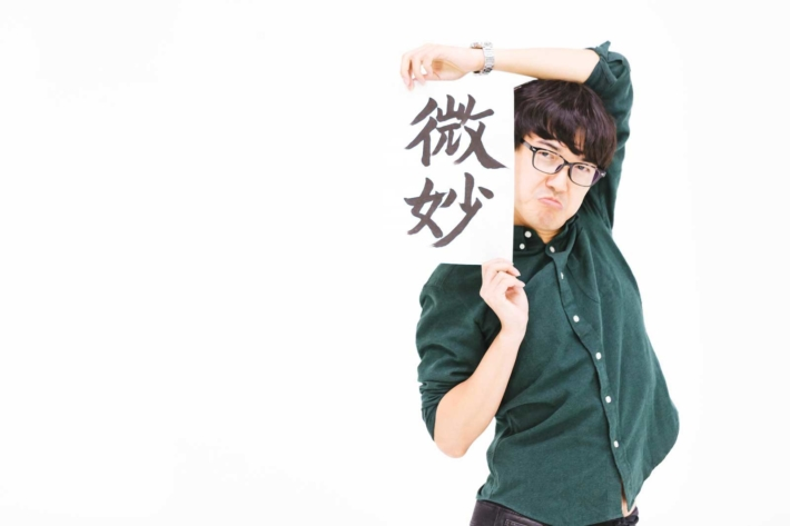 「微妙」と書かれた紙を変な恰好で持つメガネの男性
