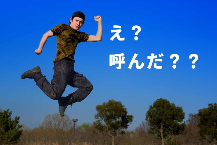 青空に向かって変なポーズでジャンプする男性と「え?呼んだ??」の文字