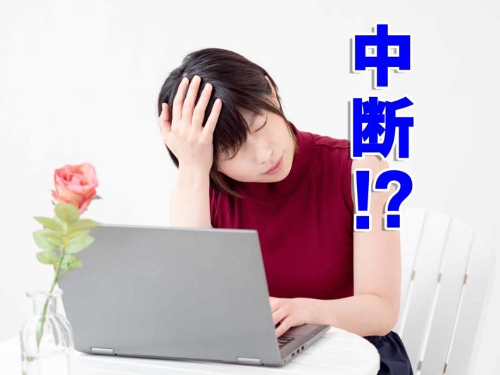 「中断!?」と書かれたテキストと、ノートPCの前で頭を抱える女性