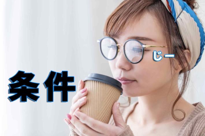 「条件」をお茶を飲みながらじーっと見つめるメガネの女性
