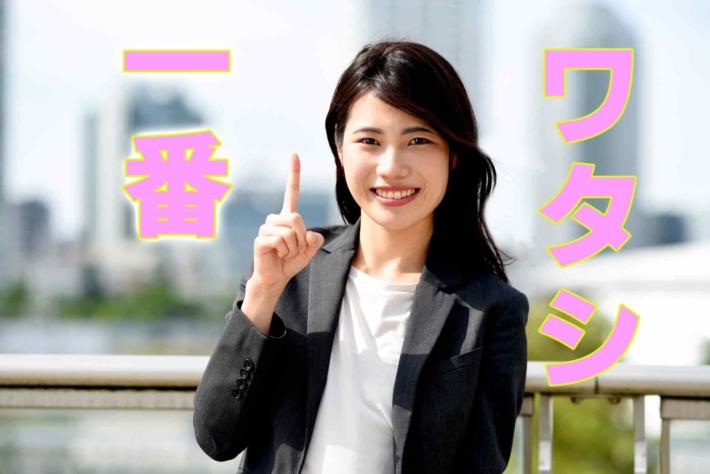 「ワタシ一番」と書かれたテキストに人差し指を立てて微笑む女性