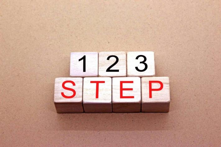 「1、2、3STEP」と書かれたブロックが机の上に置かれている画像
