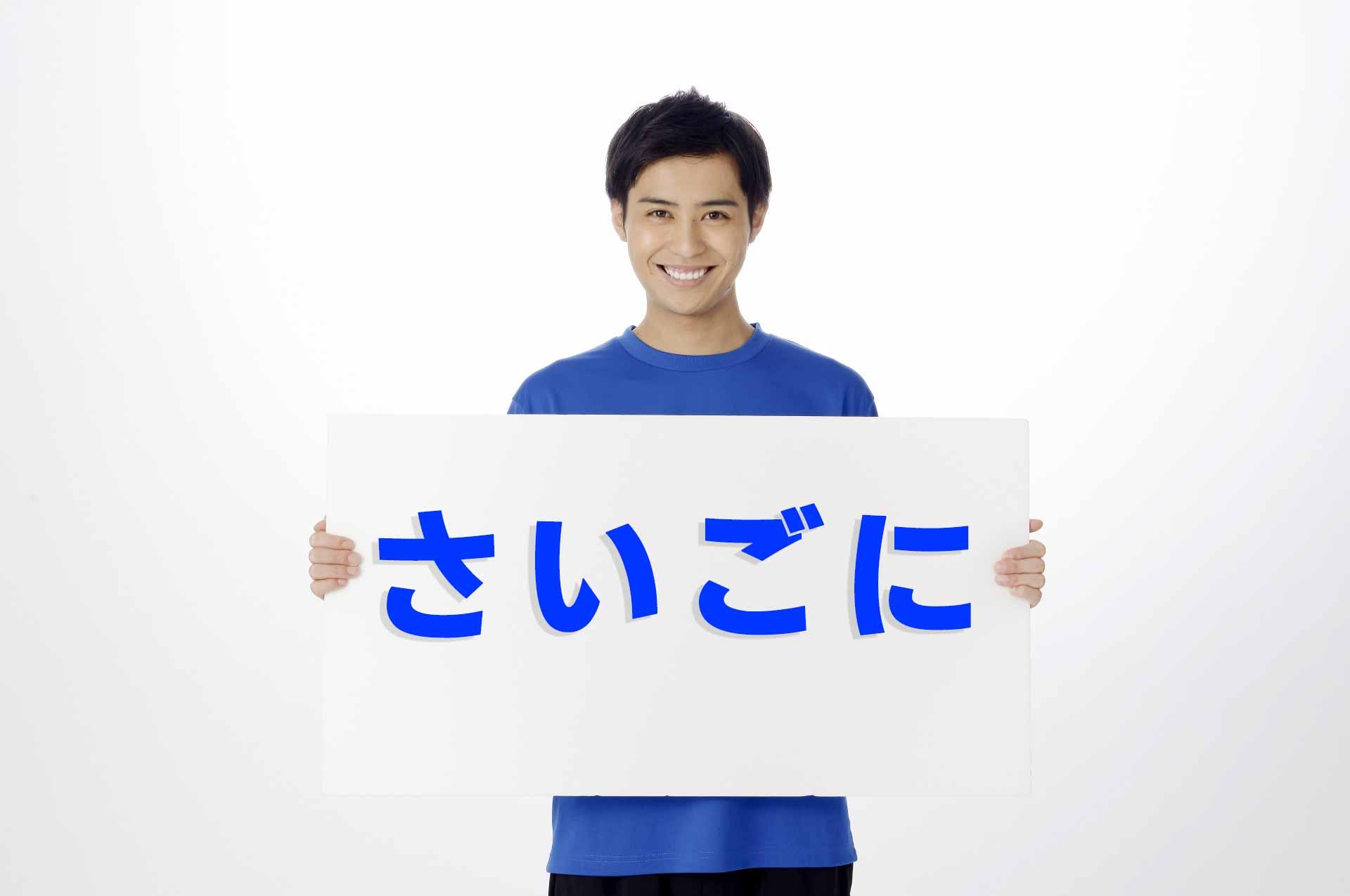 「さいごに」と書かれたプラカードを胸の前に持ち、笑顔で立っている男性