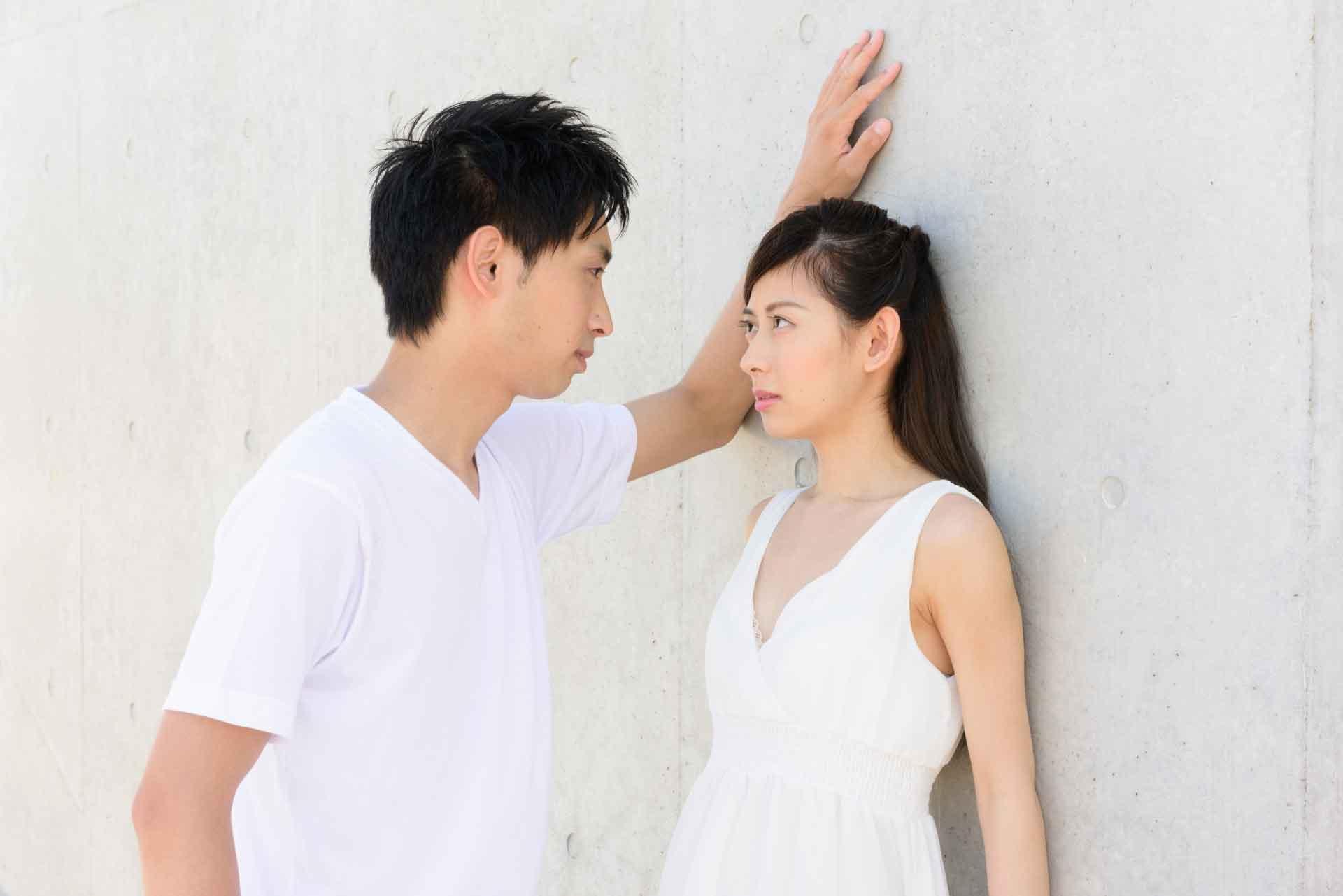 壁ドンして女性を見つめている男性