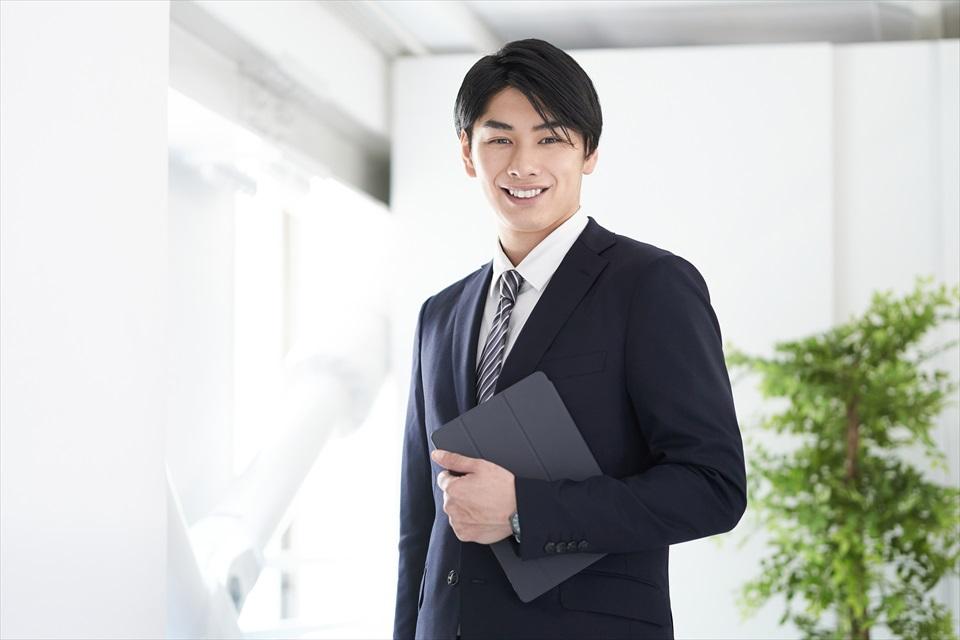 スーツ姿の男性が笑いかけている画像