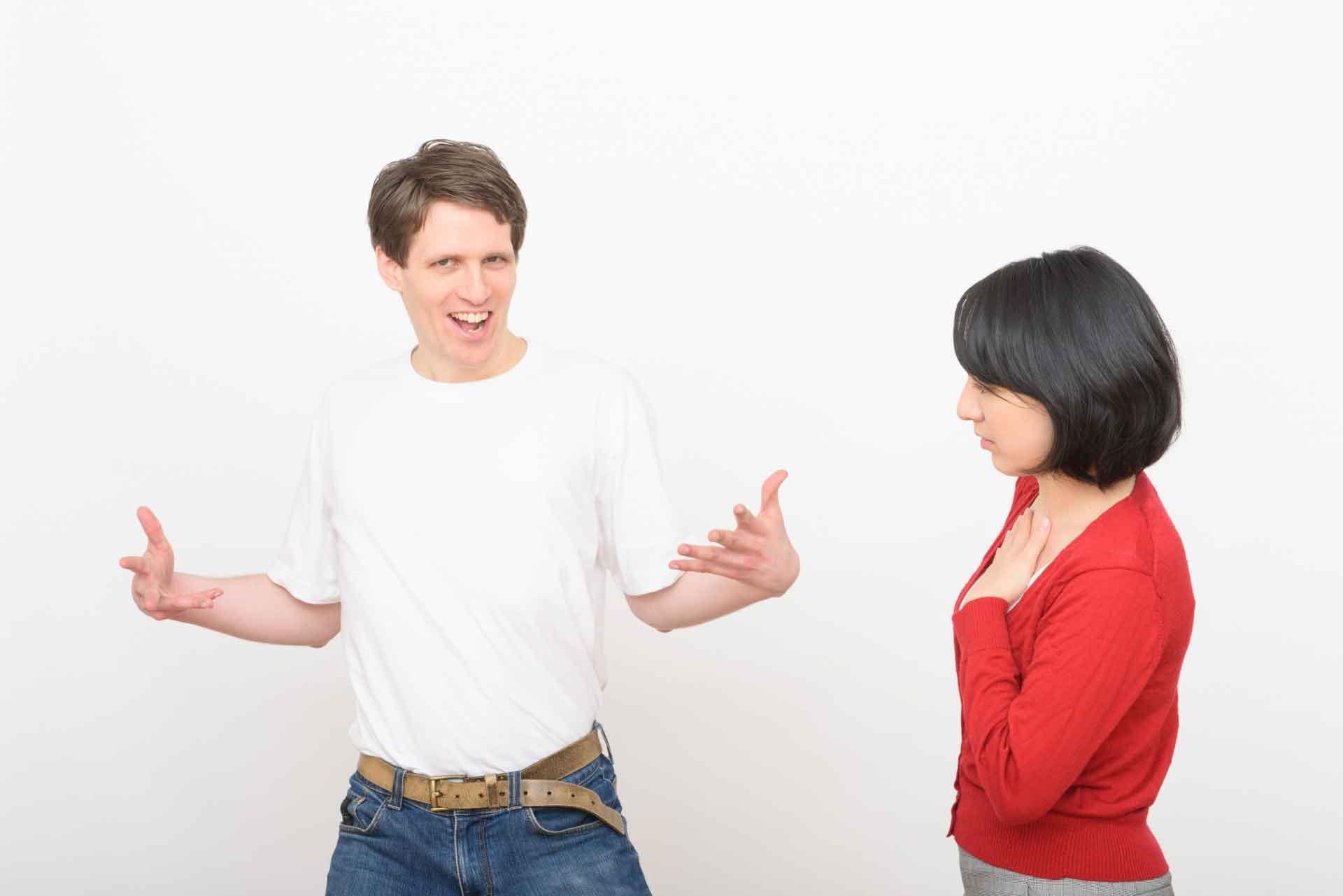 手を広げドヤっている外国人男性を冷ややかに見つめる女性