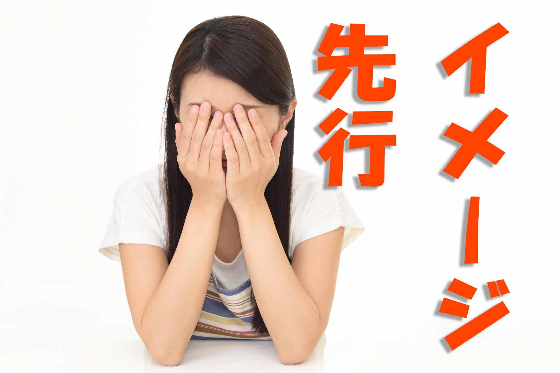 「イメージ先行」の文字と顔を覆って悩んでいる保育士の女性