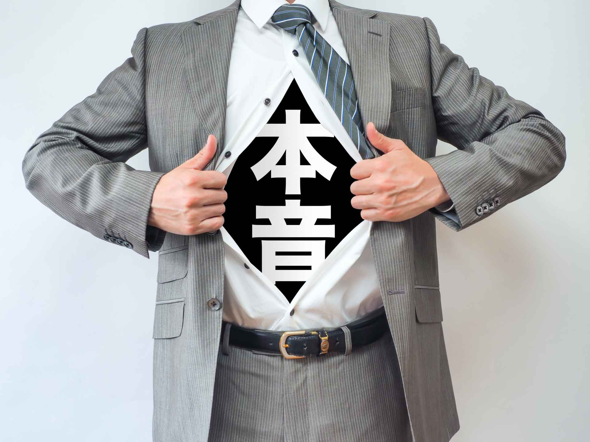 シャツを開いた部分に「本音」と書かれたスーツ姿の男性