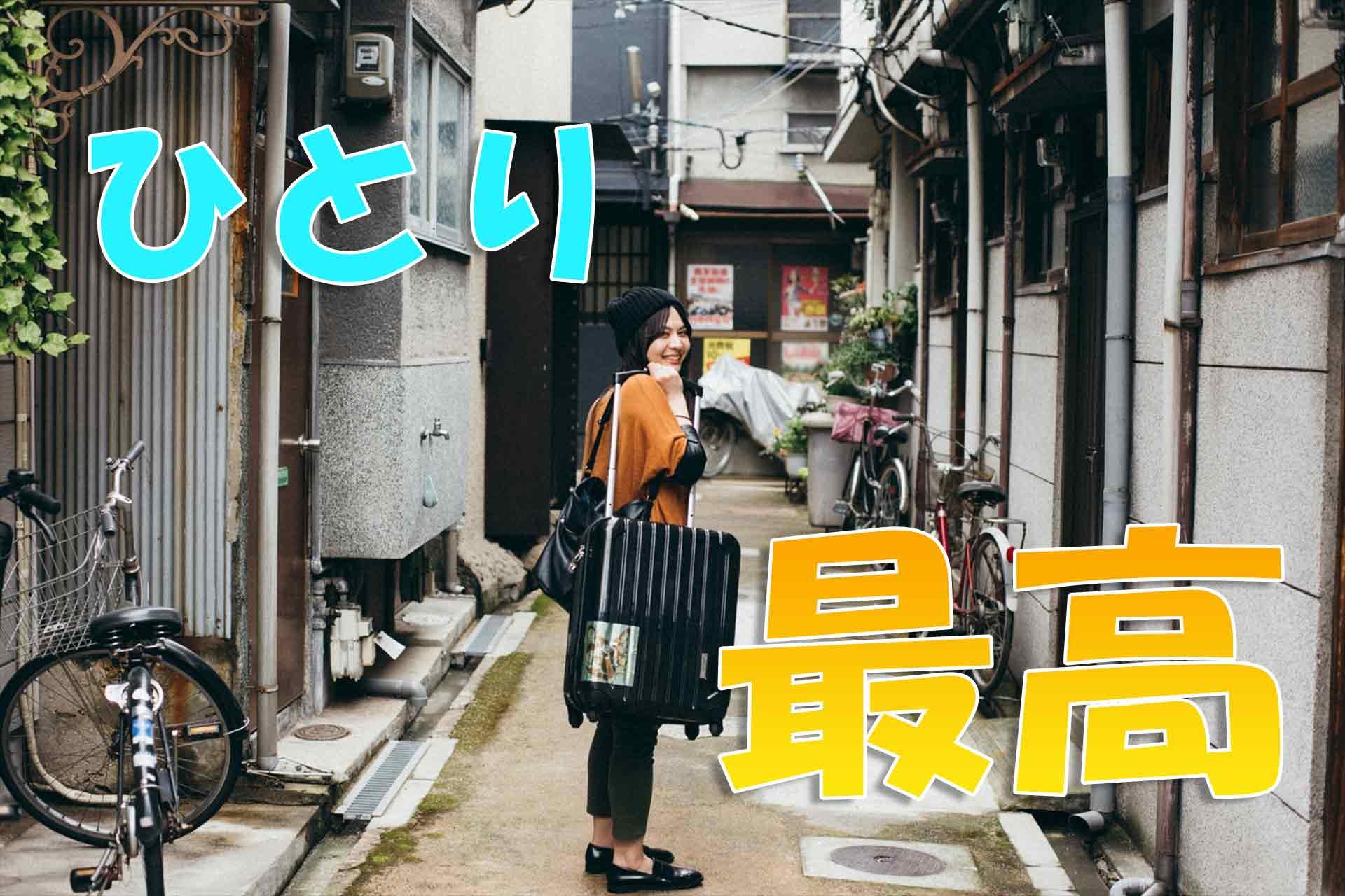 スーツケースを持ち笑顔で振り返る女性と「ひとり 最高」の文字