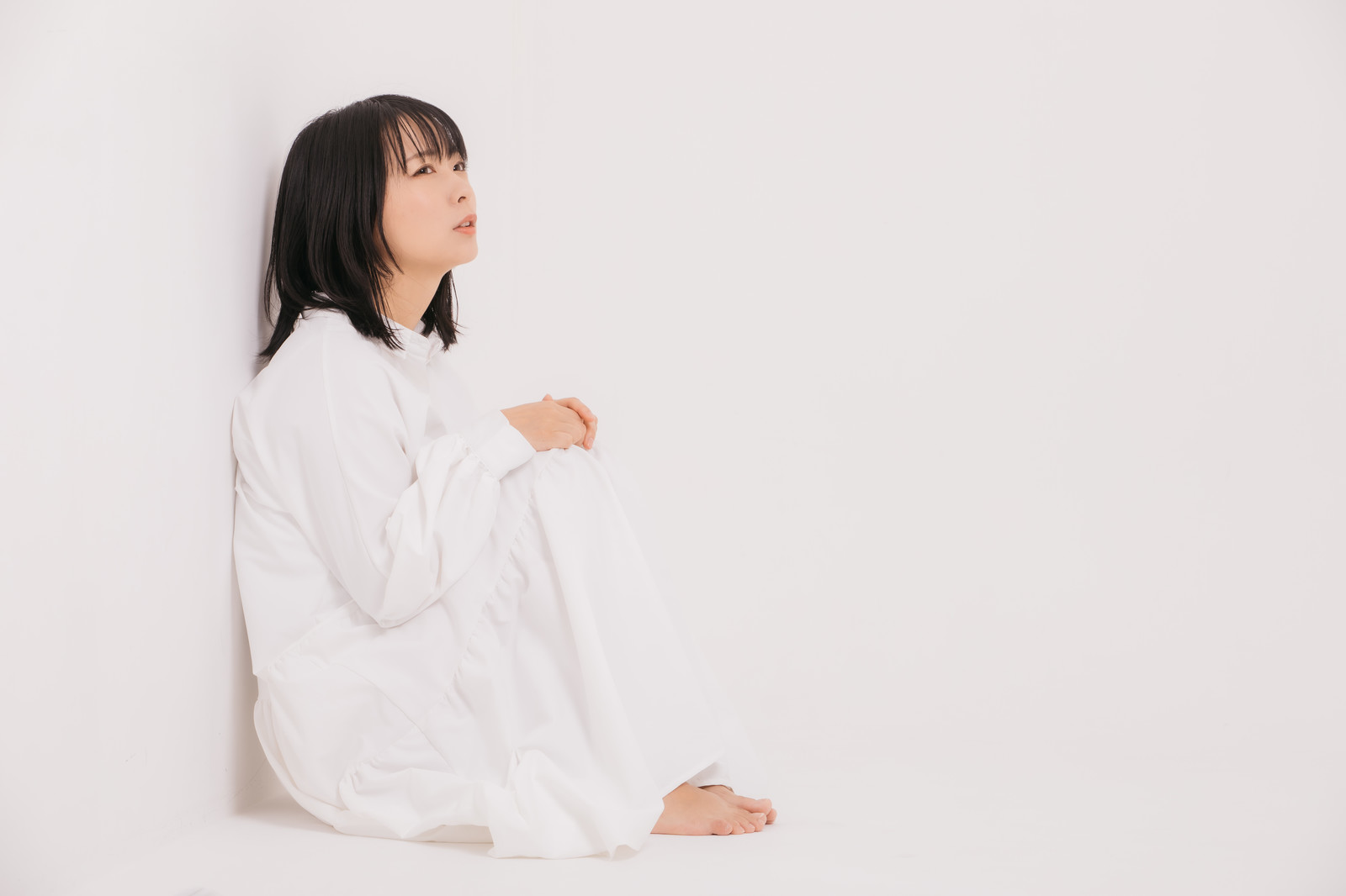 壁を背にしてパジャマ姿で天井を眺めている女性