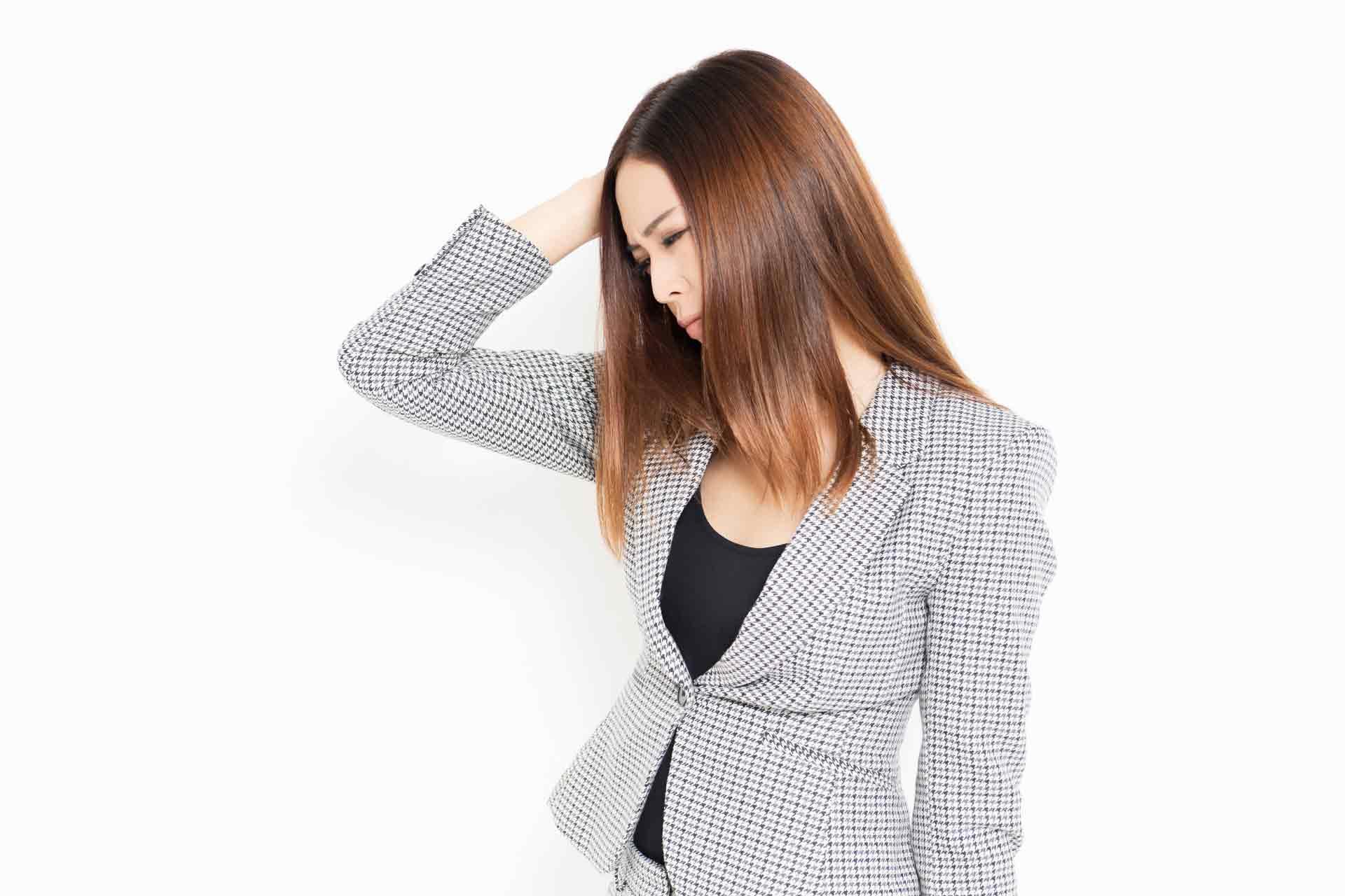 頭を抱え俯いているスーツの女性