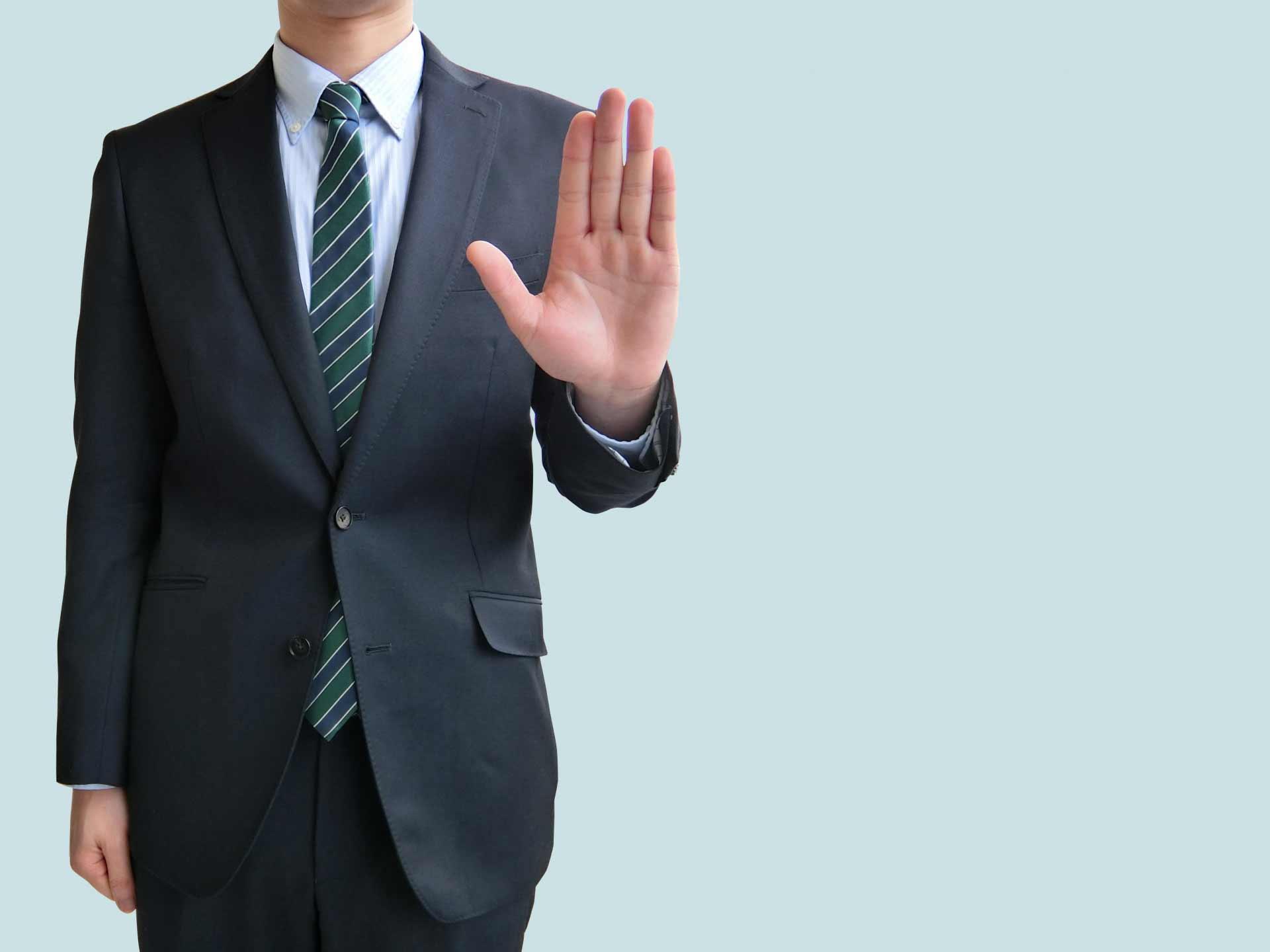 手を前に出し拒否するポーズのサラリーマン