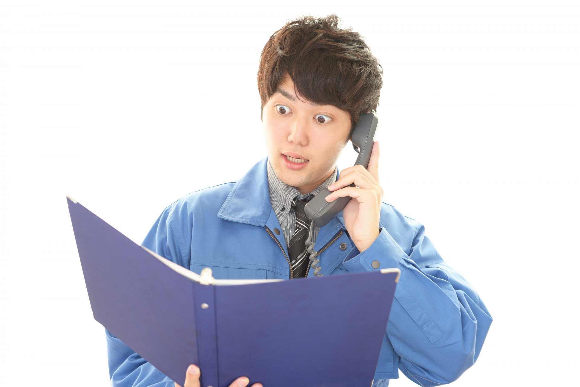 目を大きく見開いて電話をかけている男性