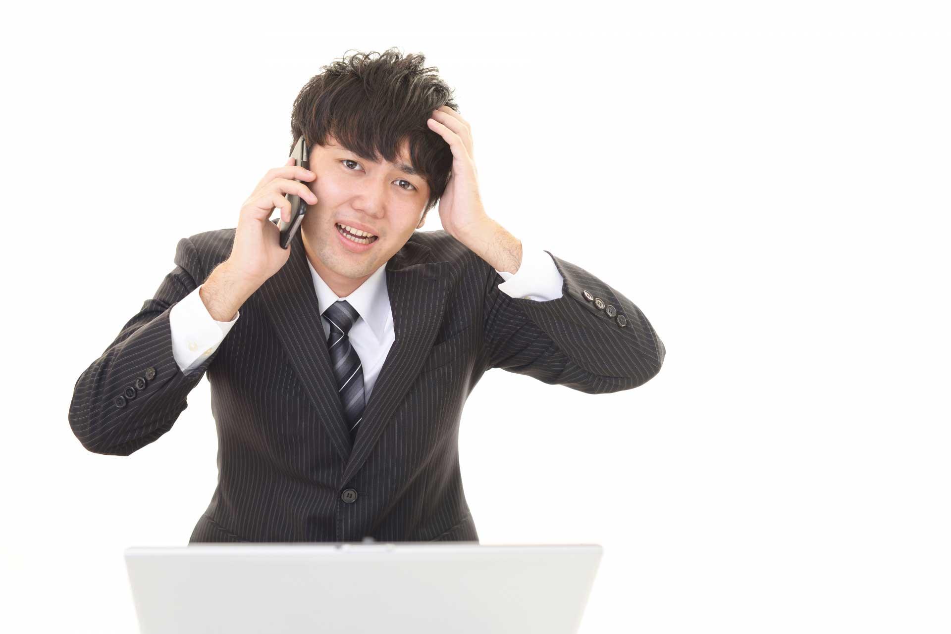 電話をしながら頭を抱えている男性
