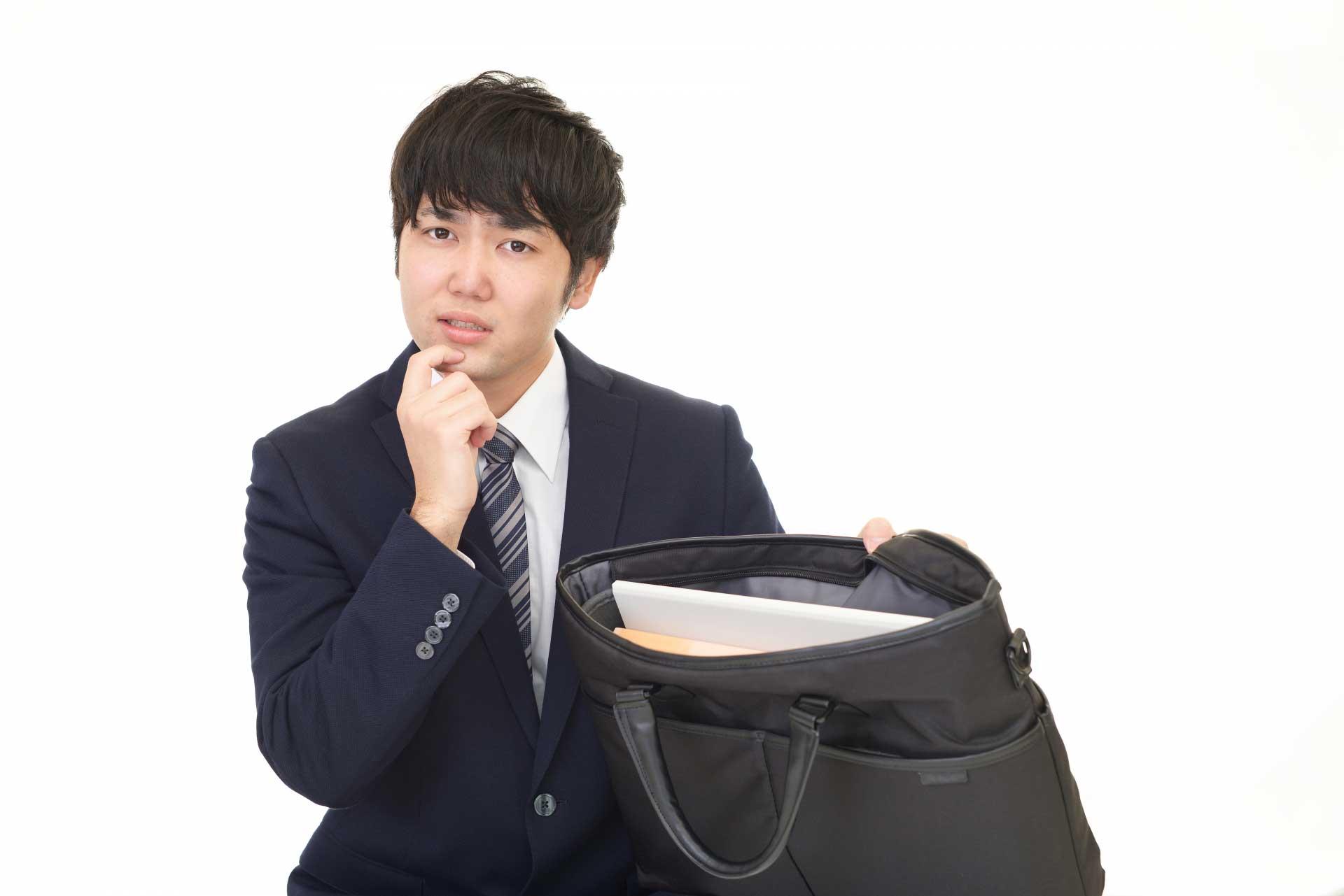 バッグの中身を見せて悩んでいる男性