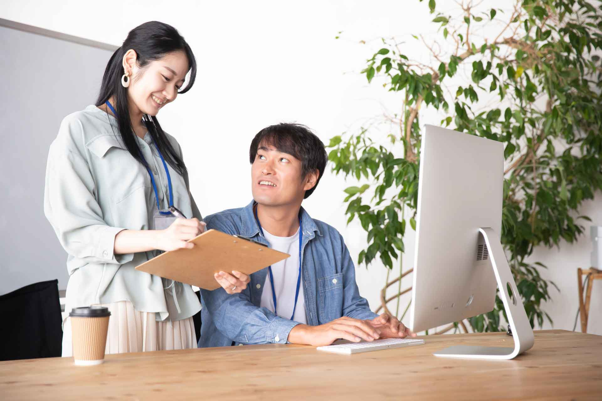 作業中の男性に話しかける女性