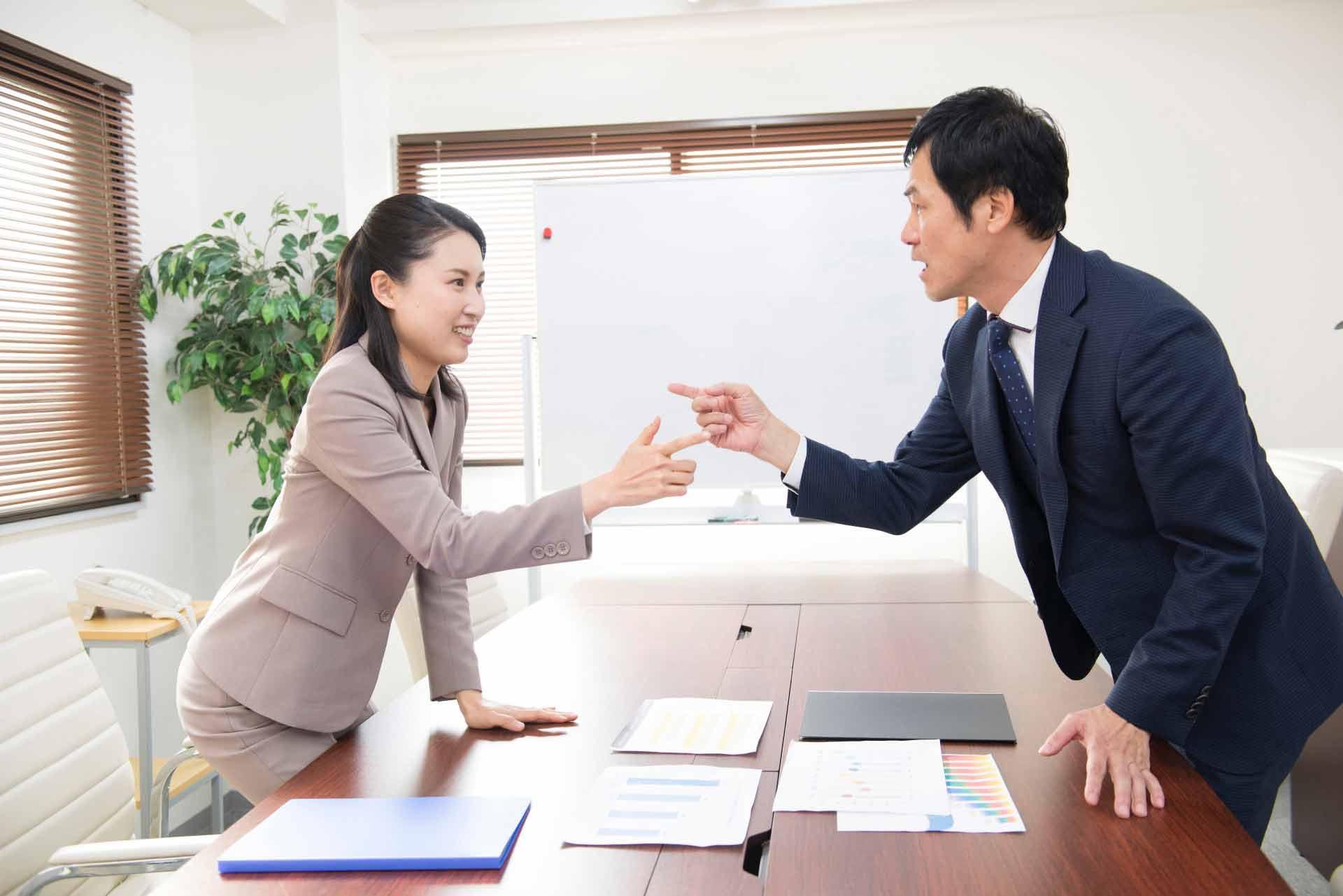 オフィスで指を指し合って言い合いしている男女