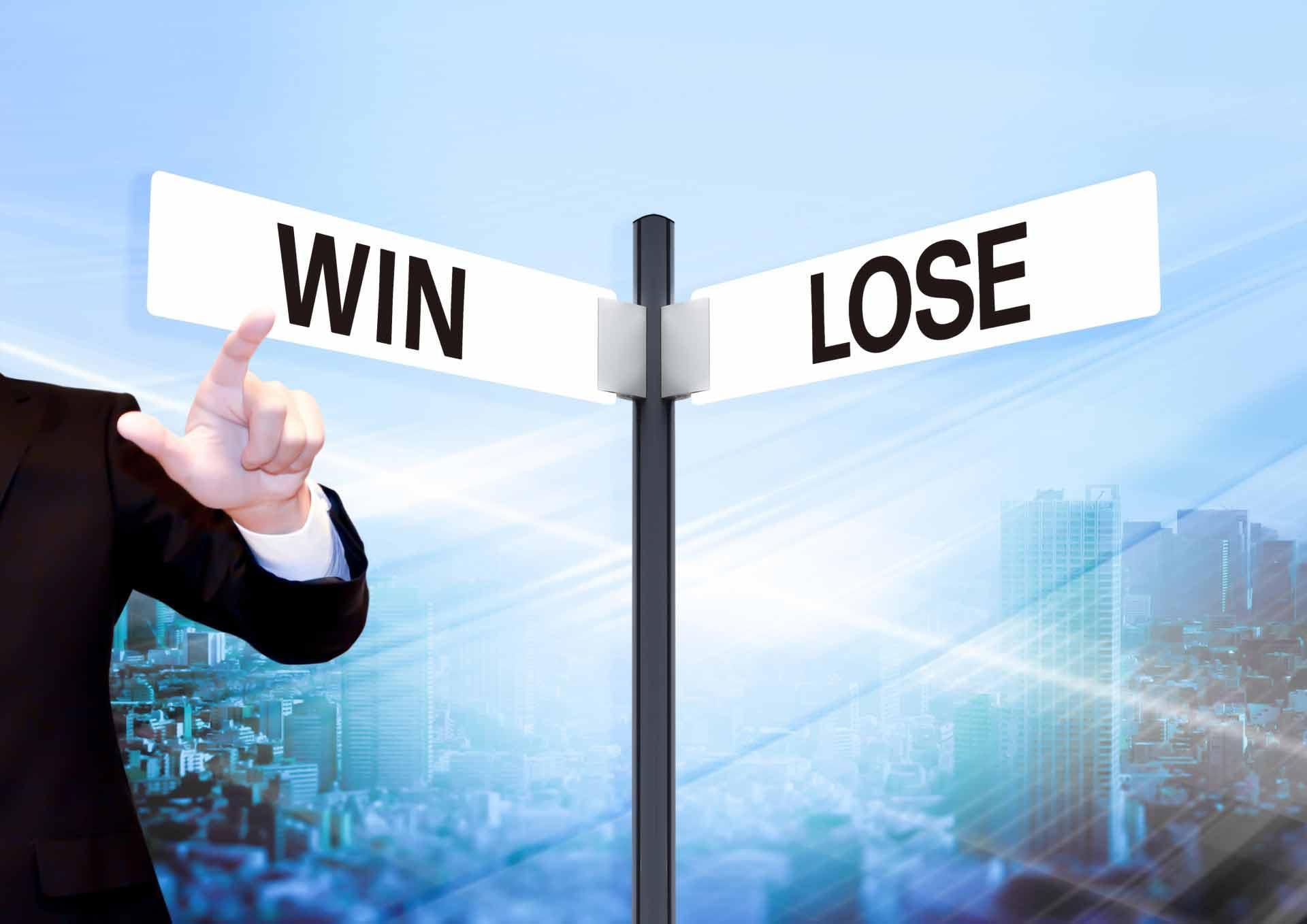 「WIN LOSE」と書かれた看板を指さす男性