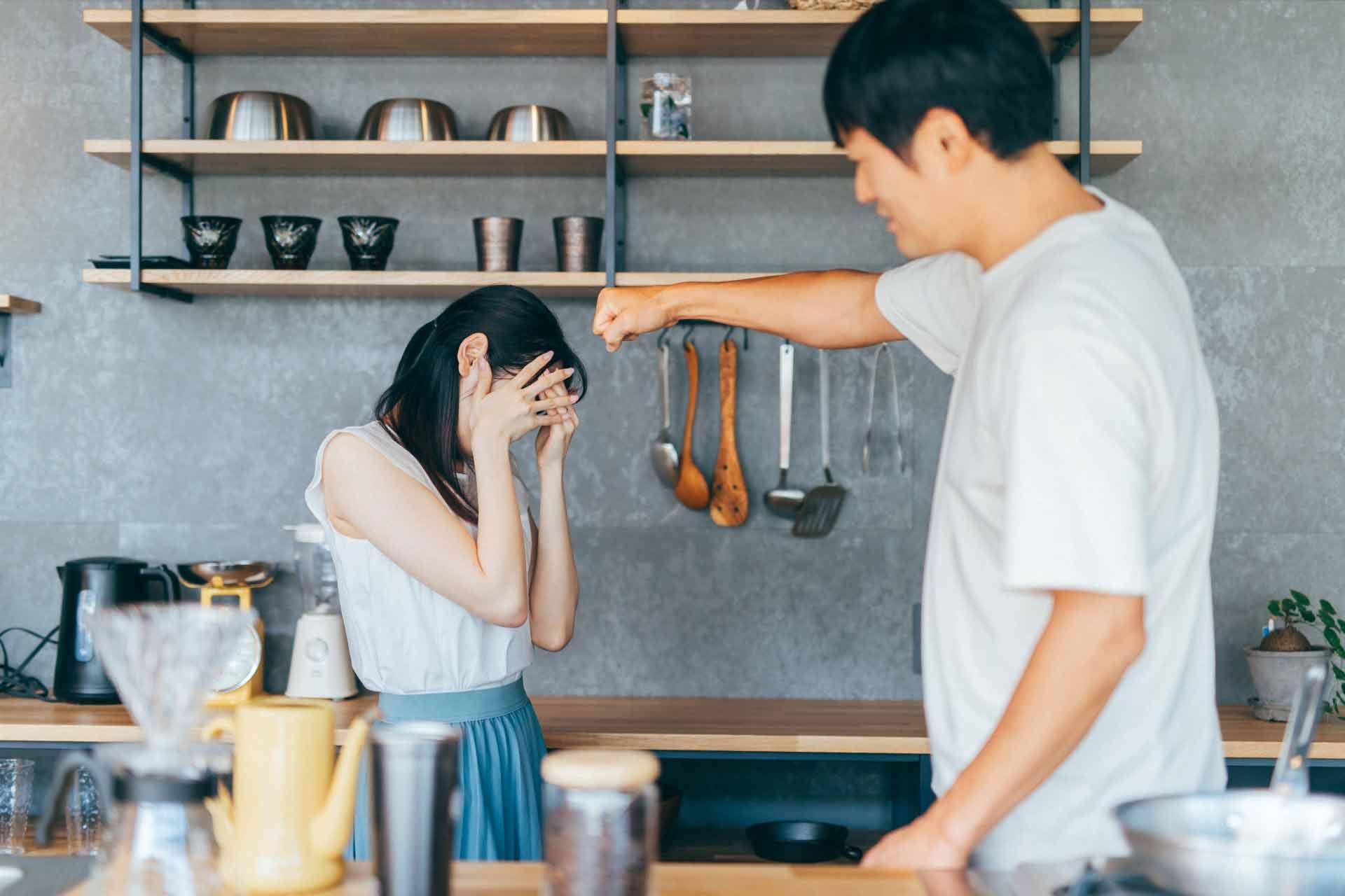 キッチンで女性に手を上げようとしている男性