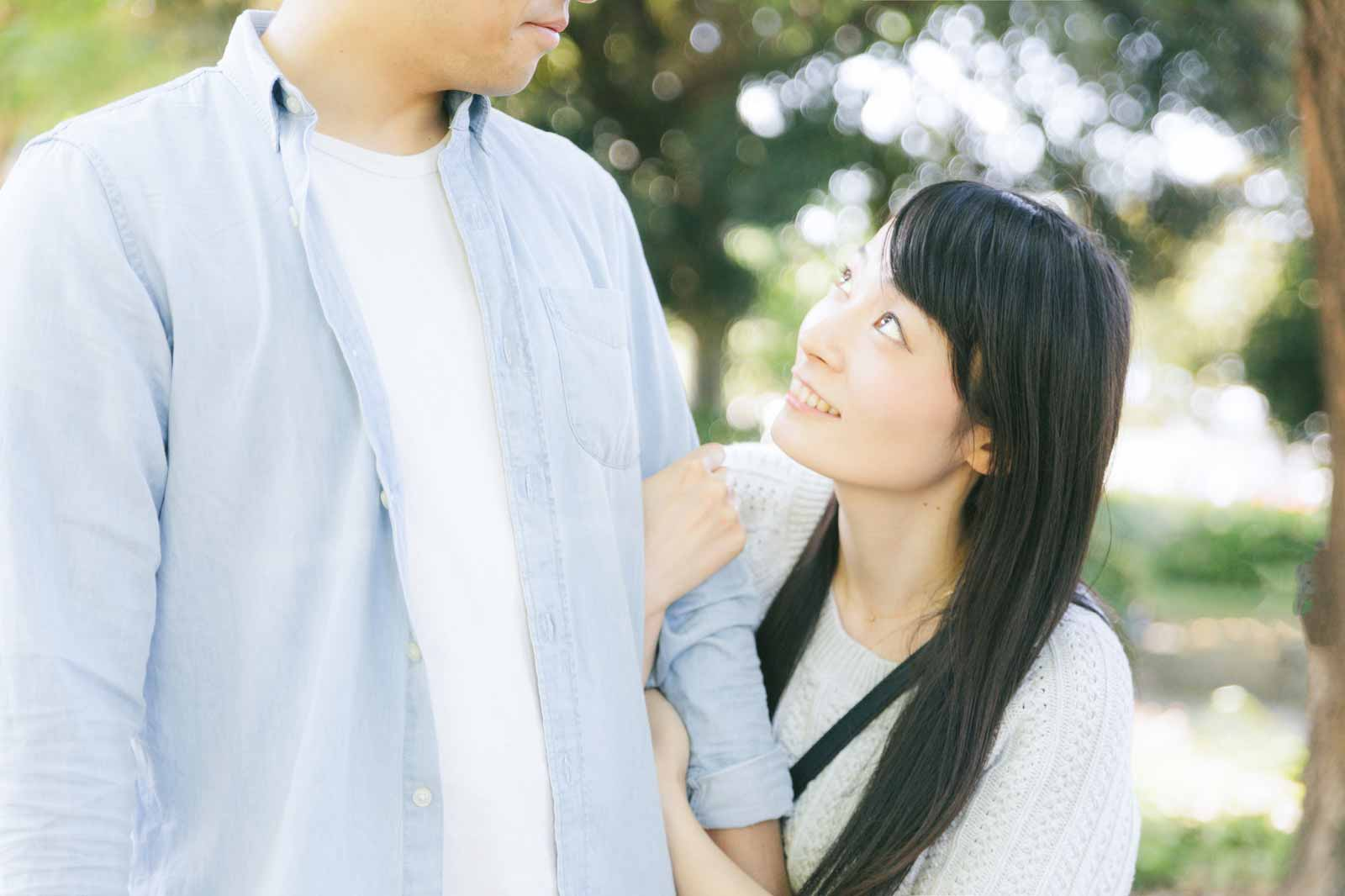 男性の左腕を持って腕組しながら、男性の顔を覗き込んでいる女性